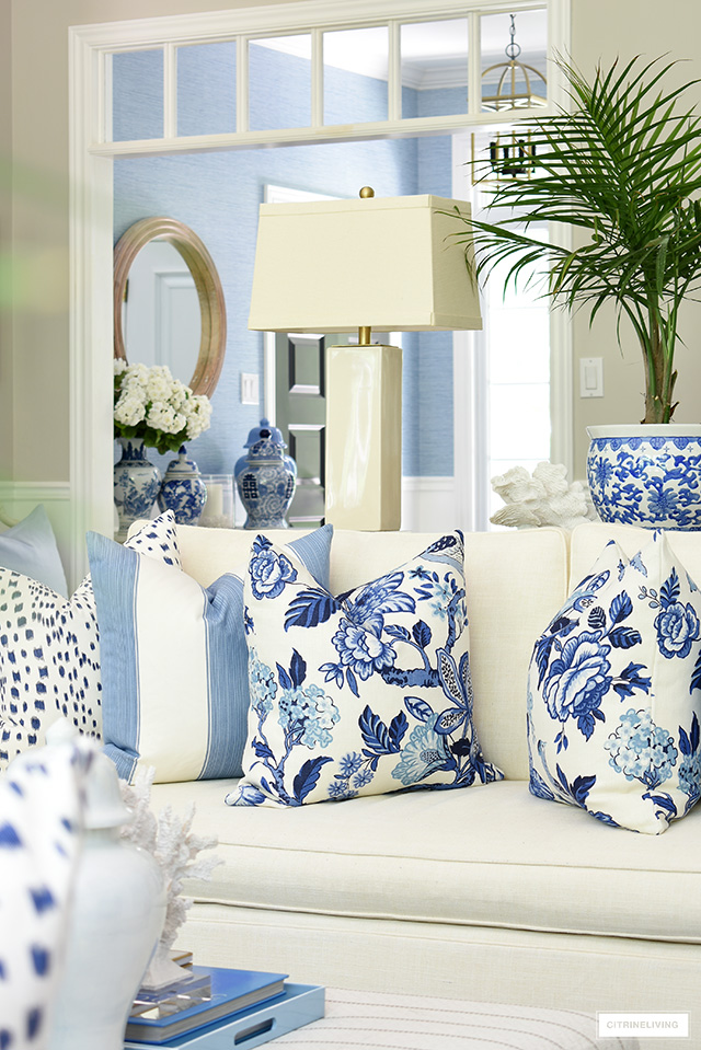 Gorgeous blue and white hamptons inspired pillows styled on a white sofa for summer.