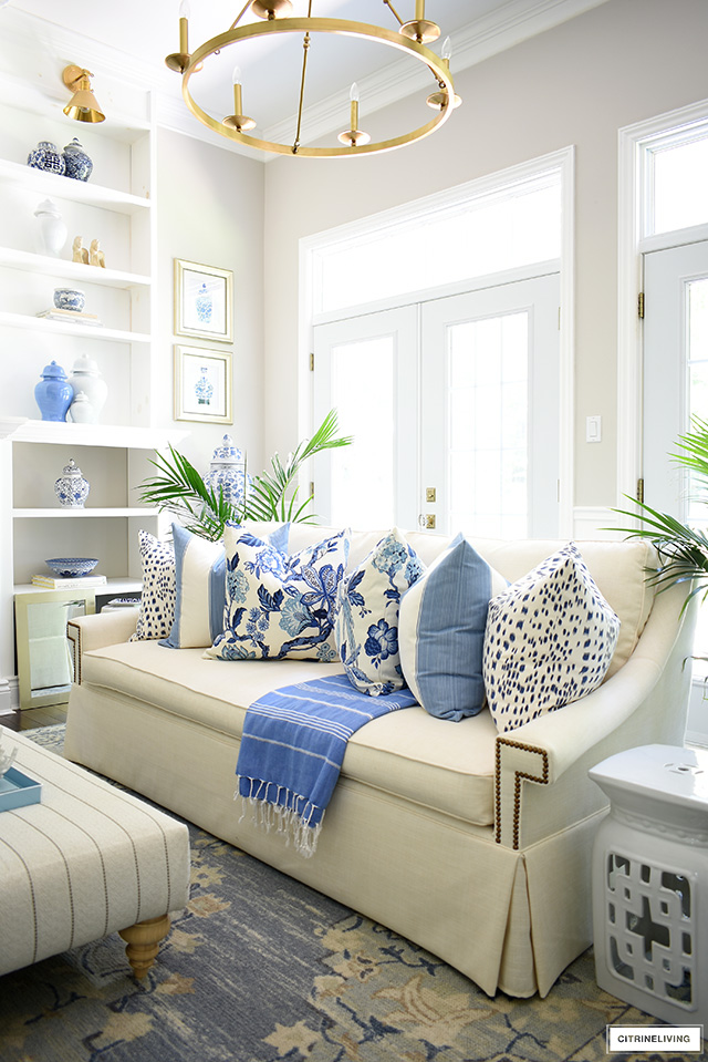 Summer decorating details: a chic white skirted sofa with blue and white hamptons-inspired pillows.