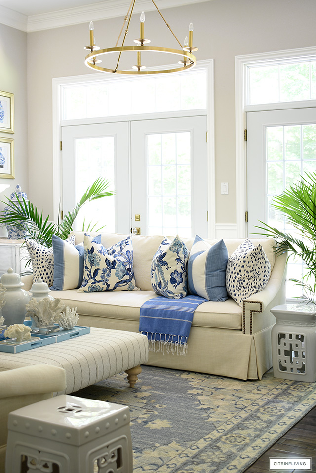 Summer styled living room in blue and white, coral sculptures and majesty palms.