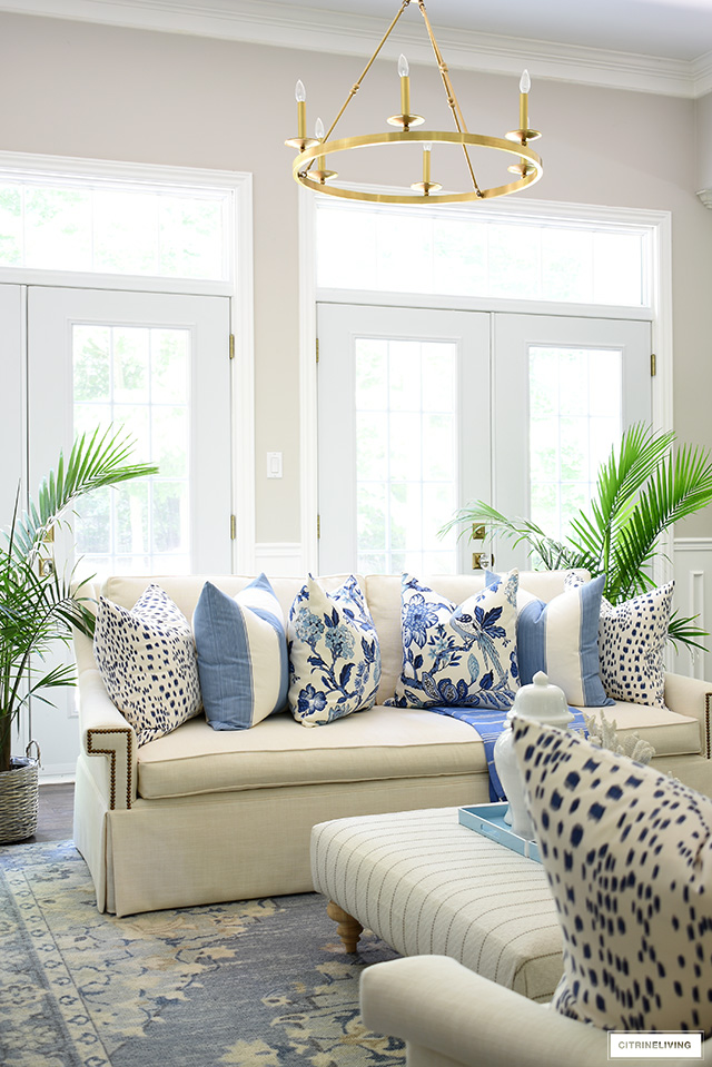 White sofa flanked with majesty palms and beautiful blue and white pillows for summer.