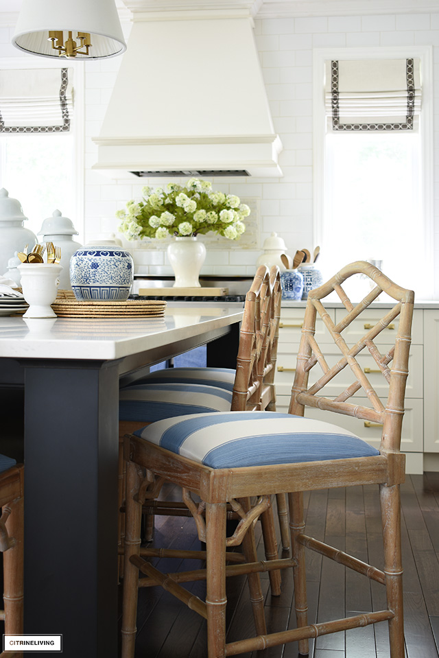 Blue and white striped fabric by Kravet covers the seats of whitewashed chinoiserie style bar stools.