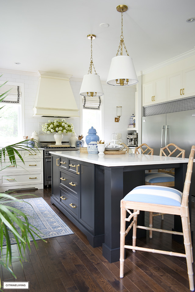 White kitchen with black island, styled for summer with blue and white accents and faux florals.