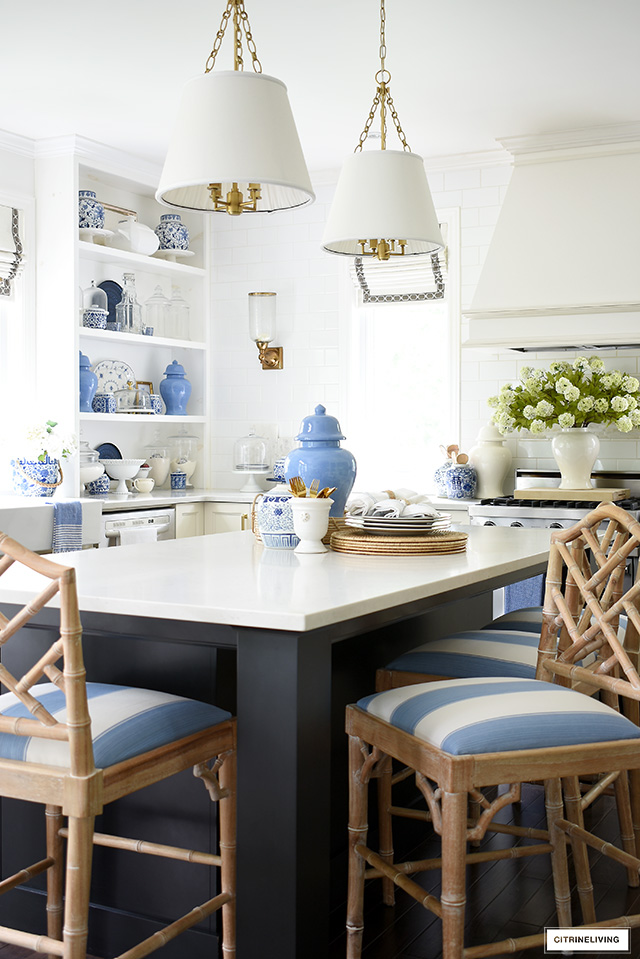 A gorgeous kitchen view of open shelves and island decorated for summer with chic blue and white accents.