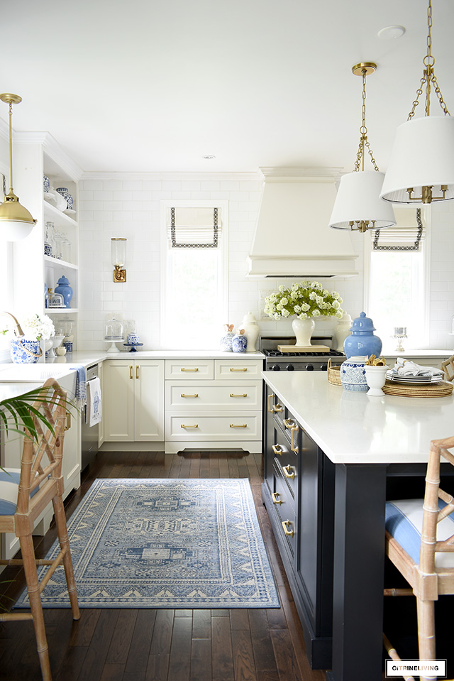 Elegantly classic kitchen styled with blue and white for summer - a blue rug, blue and white ginger jars and faux florals.