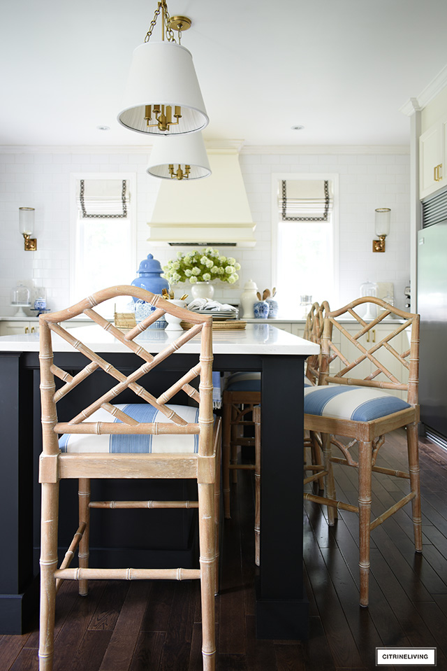 Kitchen island featuring chinoiserie chic bar stools covered in a blue and white striped fabric.