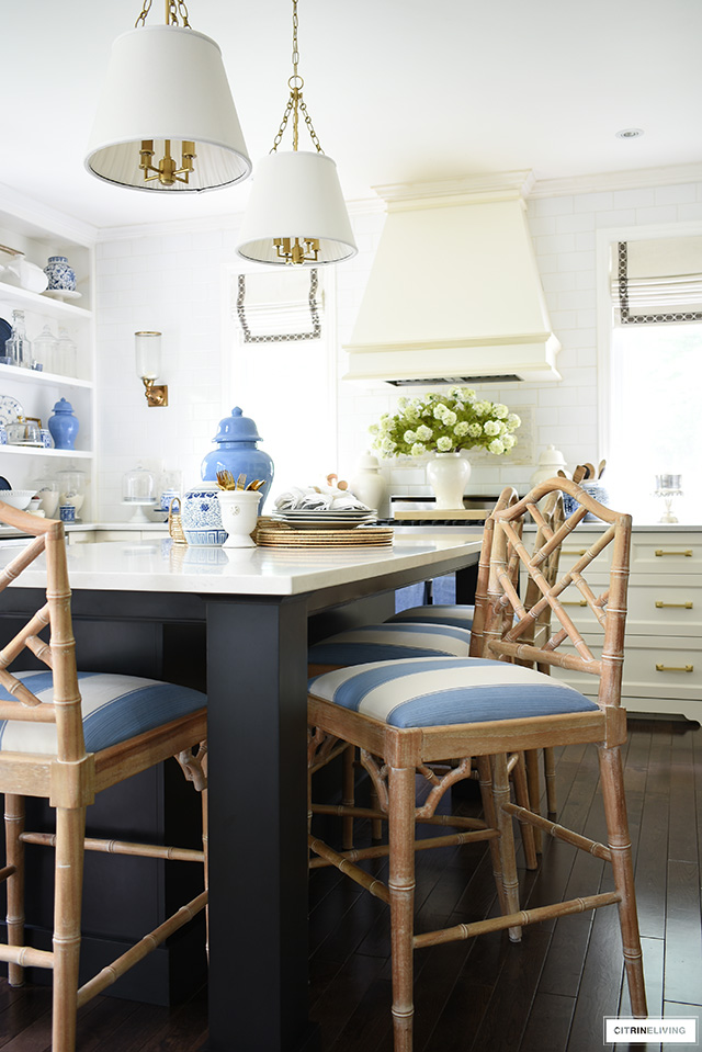 Classic kitchen decorated for summer with blue and white accents. Chinoiserie bar stools with beautiful striped fabric seat covers.