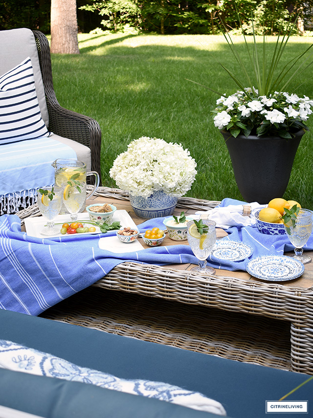 Table setting outdoors on a coffee table with pretty dishes and glasses.