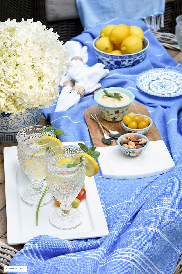 Summer table setting styled with platters, blue and white dishes and vintage inspired glassware.