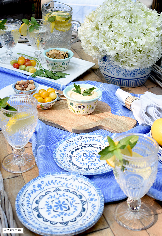 Beautiful outdoor table coffee table setting with blue and white dishes, colourful serving bowls and pretty glasses for casual dining.