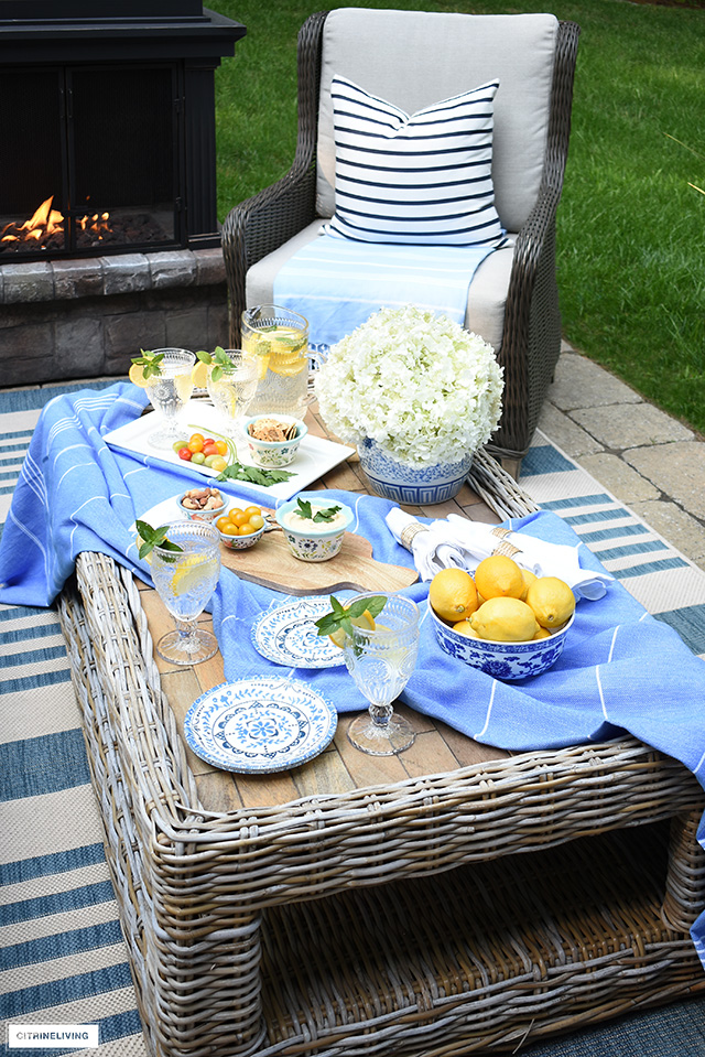 Outdoor coffee table styled for summer entertaining with pretty dishes and glasses.