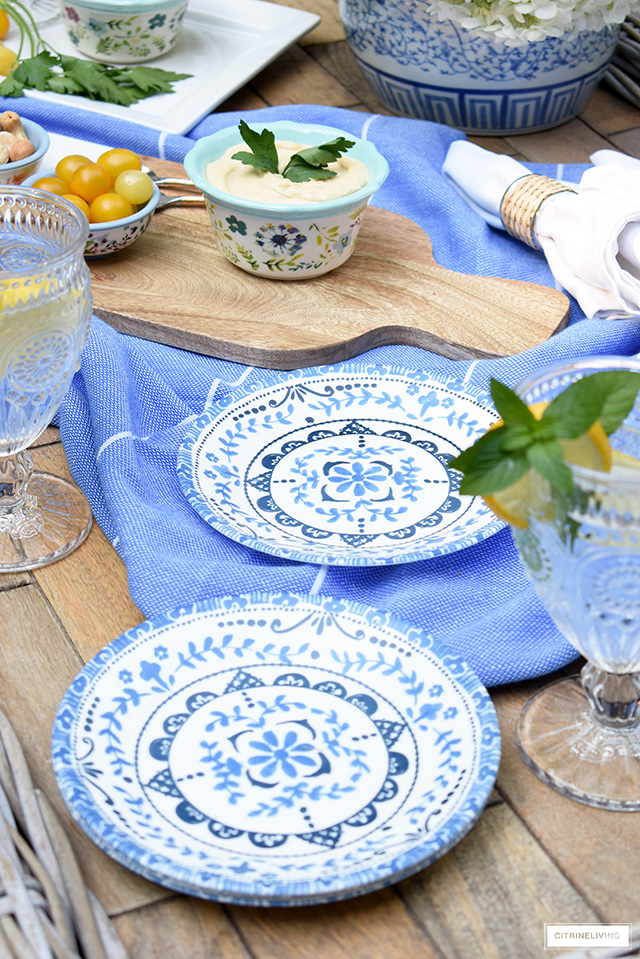 Outdoor table styled with blue and white dishes for casual and elegant dining.