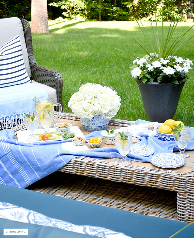 Outdoor coffee table styled with beautiful glasses and dishes for summer entertaining.