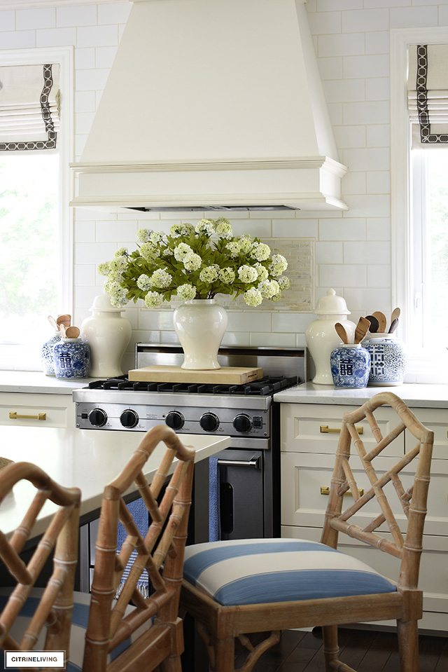 Kitchen stove decorated with ginger jars and faux florals for summer.