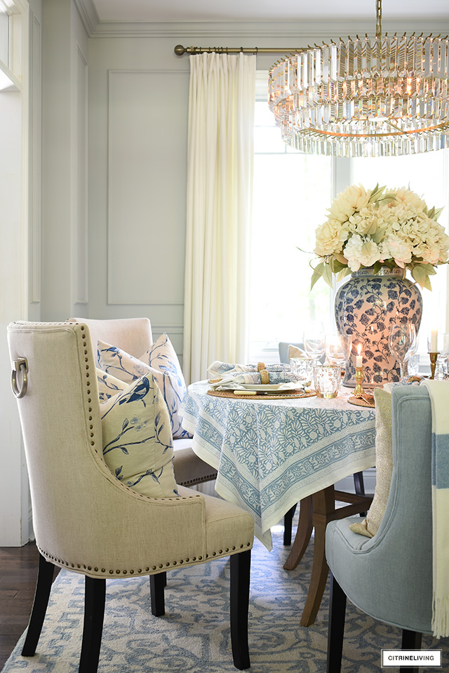 Fall dining room decor and tablescape with blue chairs, rug and table linens mixed with warm neutral tones.
