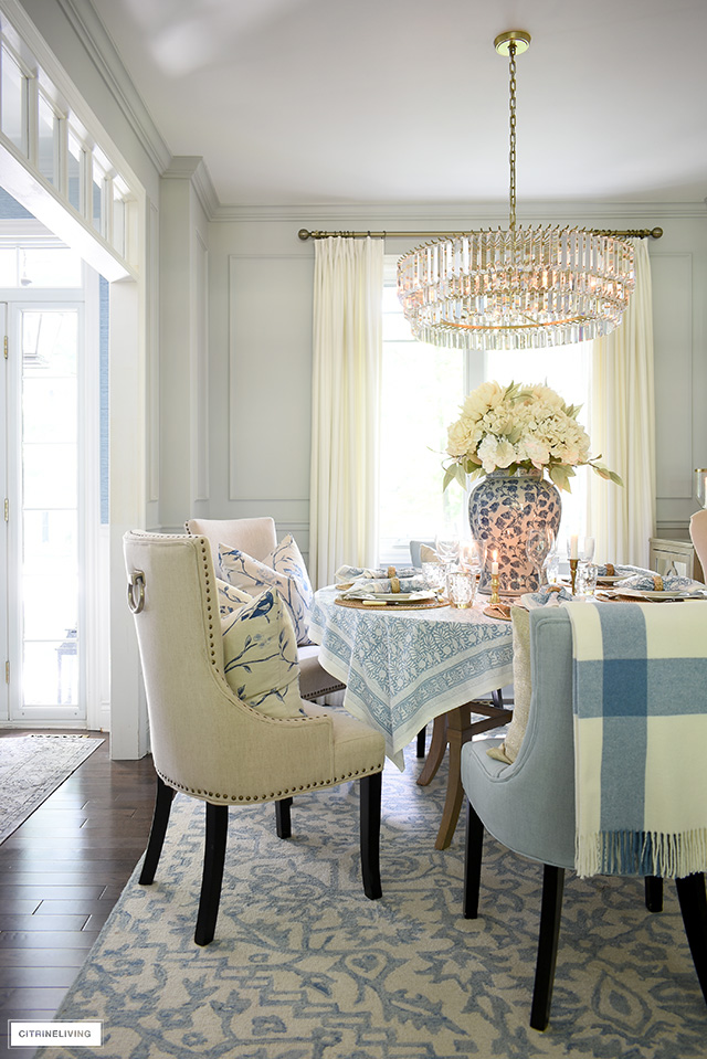 Dining room decorated for fall in neutral tones and soft blue hues.