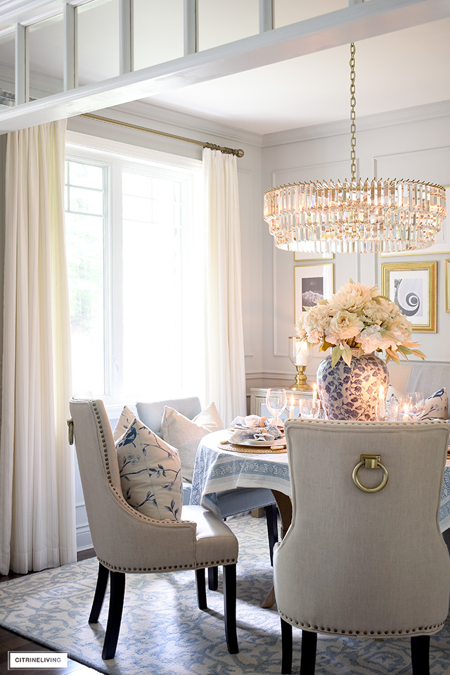 Dining room decorated for fall with layers of soft blues and neutral tones.