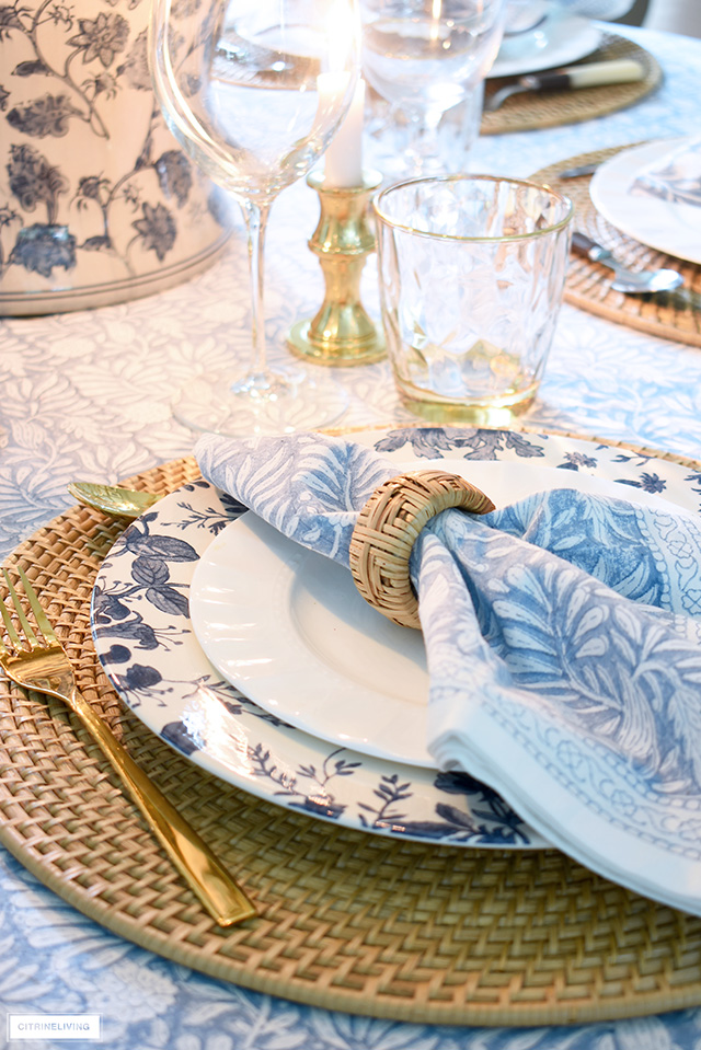 Fall table setting with woven placemats, blue and white floral dishes and block print blue linens.