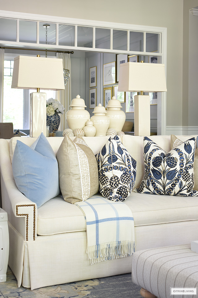 Beautiful living room details for fall with white sofas styled with blue and warm neutral pillows, ginger jars and plaid throws.