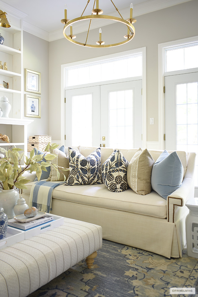Living room decor with a blue and beige color palette - designer pillows, faux leaves and simple seasonal touches.