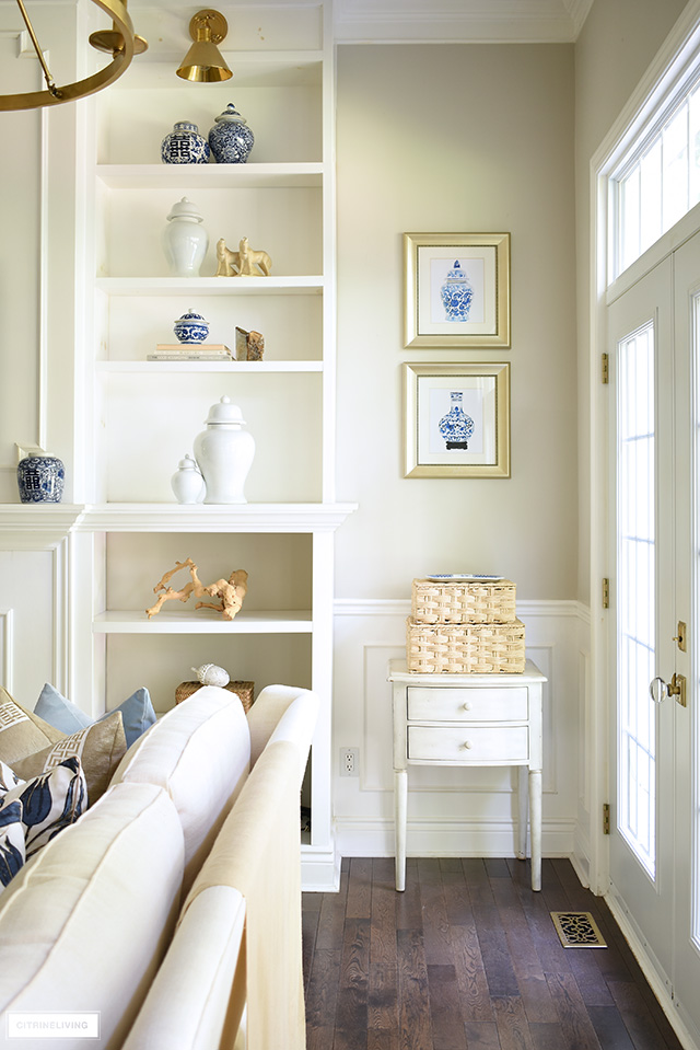 Living room bookshelves styled for fall with ginger jars, simple fall touches and warm accents.