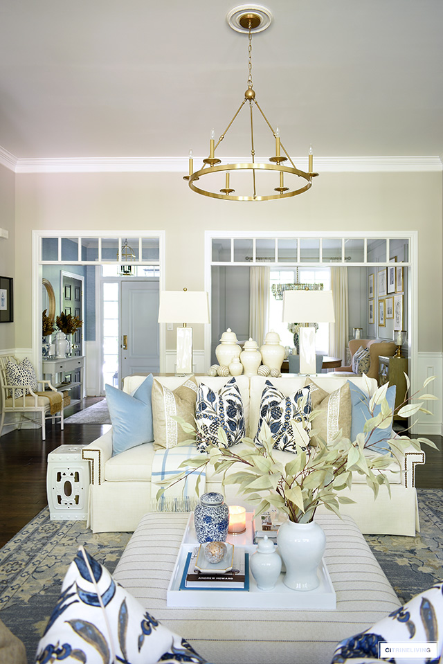 Living room sofa styled with designer throw pillows, ottoman/coffee table styled with white trays and seasonal accents.