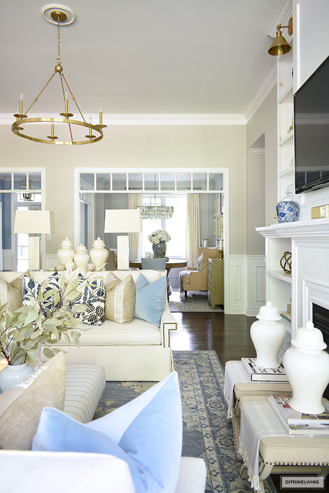 Living room styled for fall with elegant pillows in blues and warm neutrals, ginger jars and simple seasonal decor.