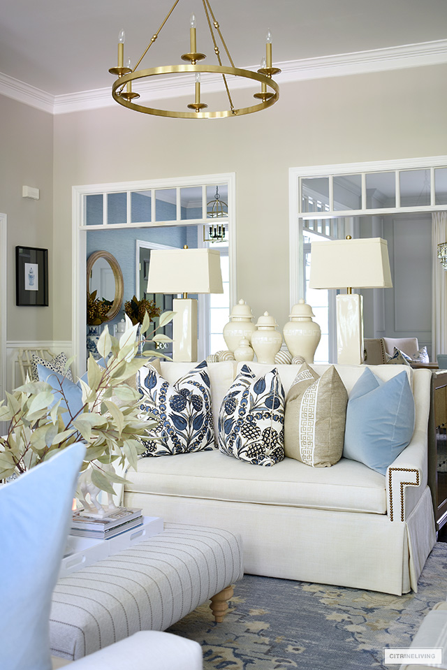Living room styled for fall with beautiful designer pillows in blues and warm neutrals, on a white sofa.