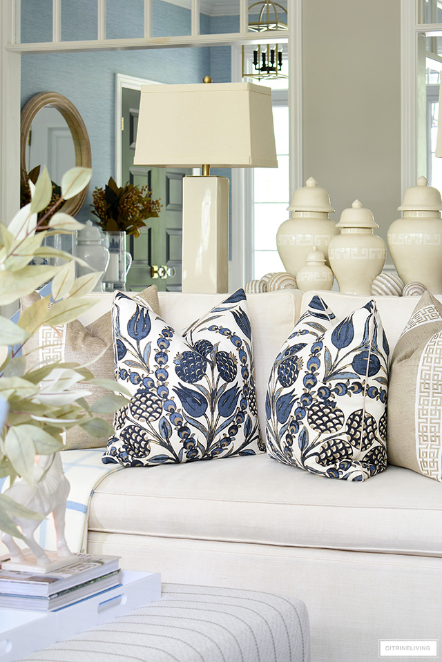 Living room styled for fall with gorgeous navy blue and beige printed pillows.