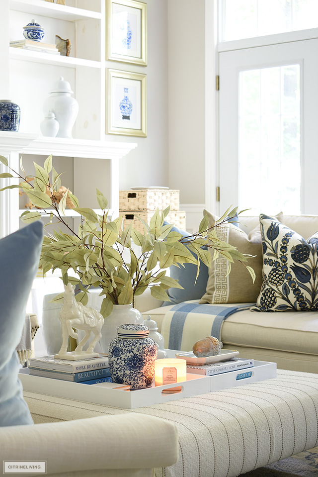 Fall living room details - ottoman styled with trays, ginger jars, faux fall foliage and seasonal accessories.