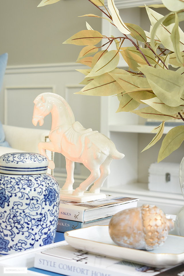 A beautiful horse sculpture styled on a tray with design books and fall accents.