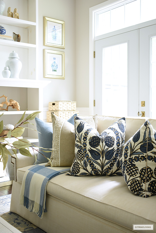 Beautiful designer pillows styled on a white sofa with a plaid throw for fall.
