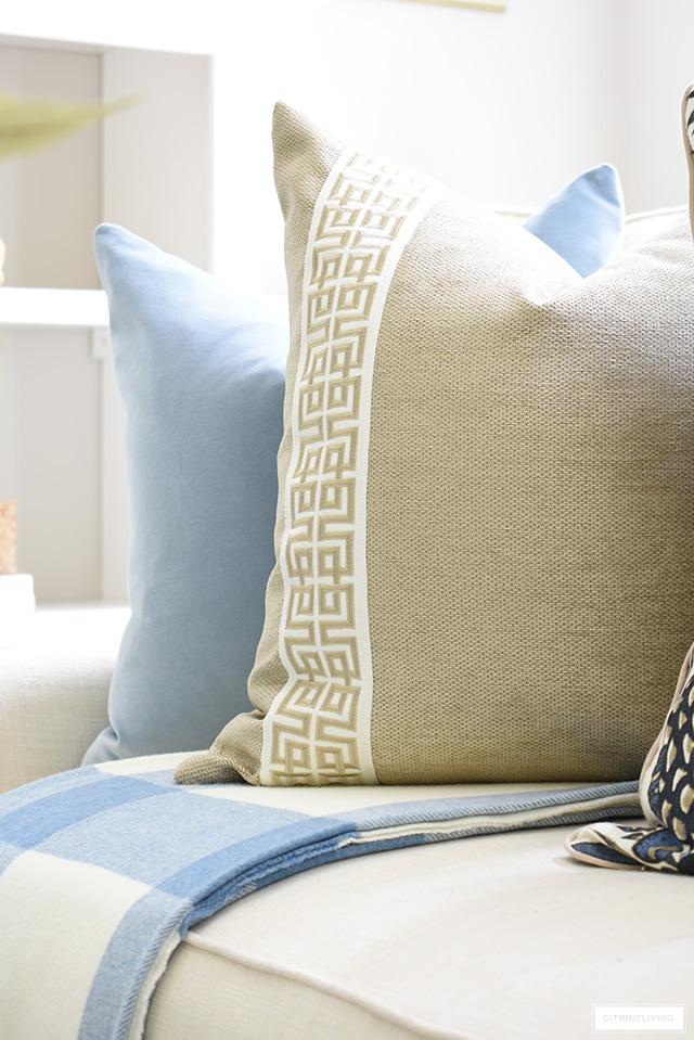 Elegant designer pillow in a beige shimmer fabric with greek key ribbon detailing.