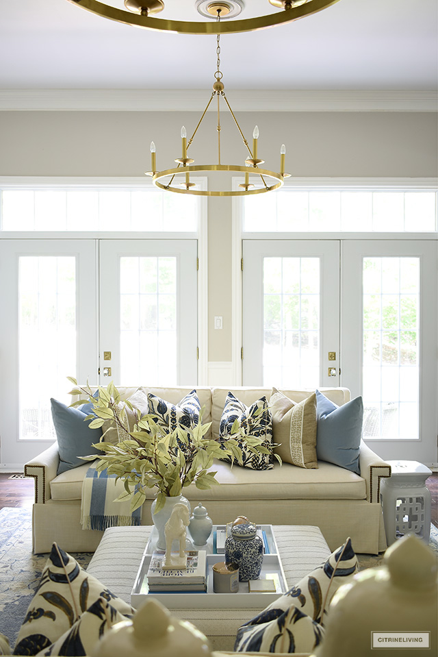 Fall decorated living room with white sofas, blue and beige pillows, faux leaves and simple seasonal accents.