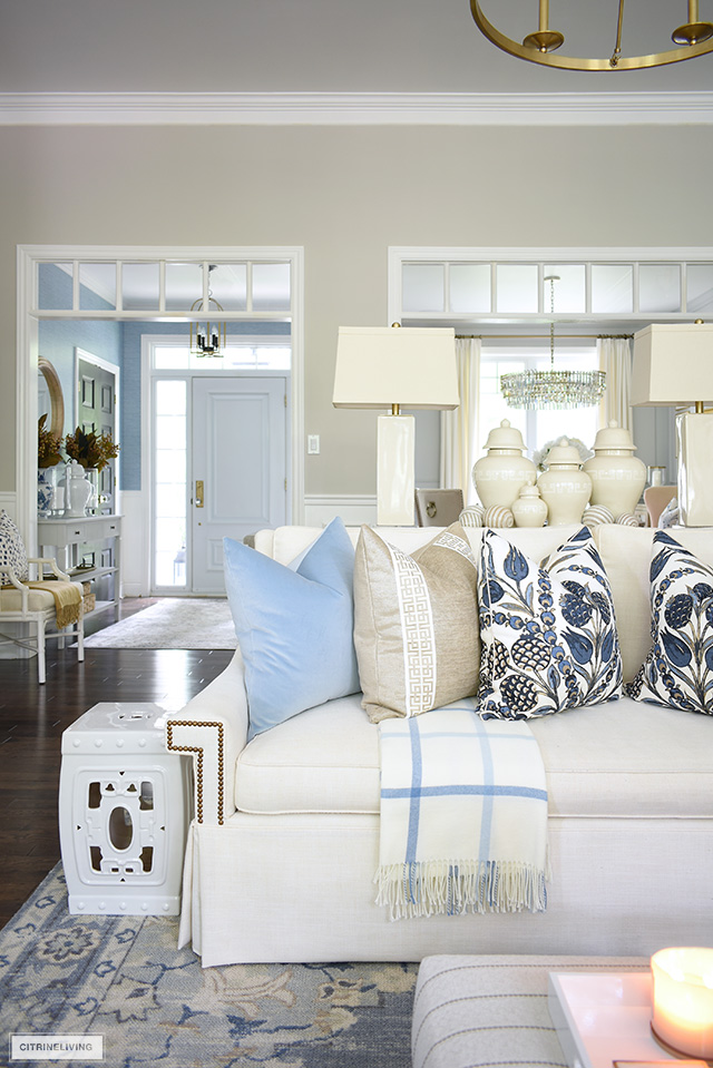 Living room decorated for fall with white sofas and designer pillows, accented with elegant ginger jars.