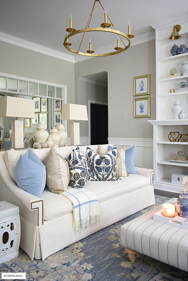 Gorgeous designer pillows in blues and warm neutrals styled with a cozy plaid throw for fall.