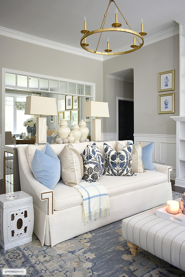 Fall living room decor, white sofa styled with designer pillows in blues and beiges.