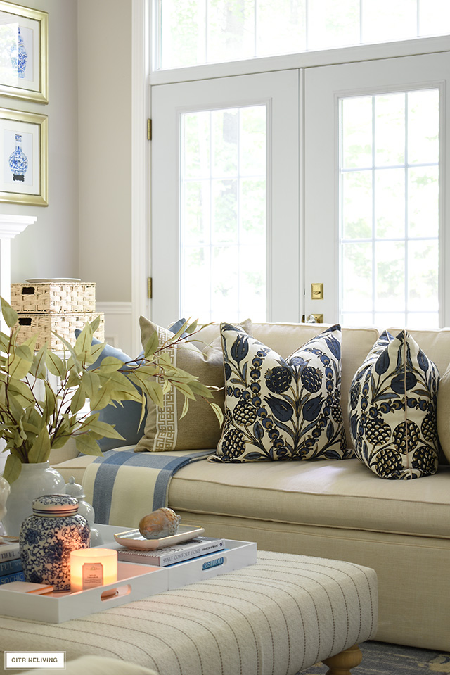 Elegant designer throw pillows styled on a white sofa, ottoman styled with faux leaves and simple fall accents.