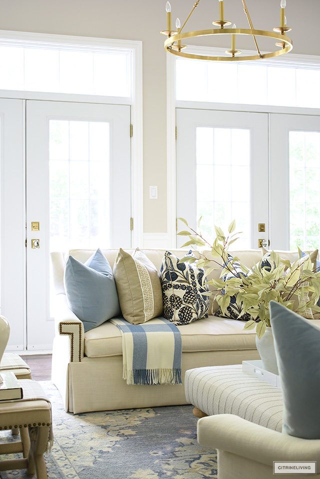 Fall living room decor with white sofas styled with blue and beige designer pillows and throw blanket.