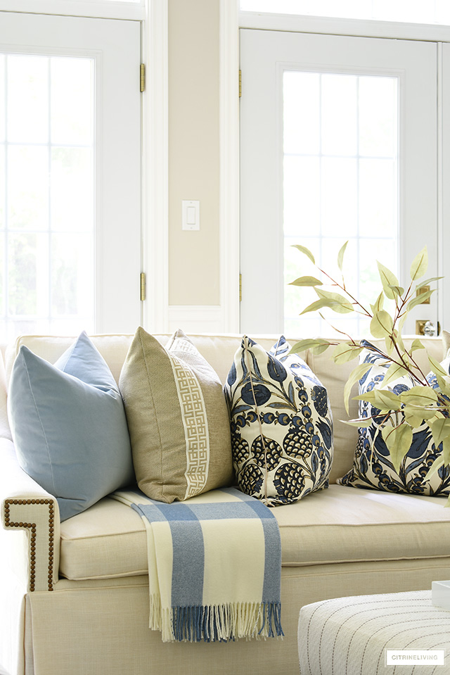 Designer throw pillows and blanket in blues and warm neutrals styled on a white sofa for fall.