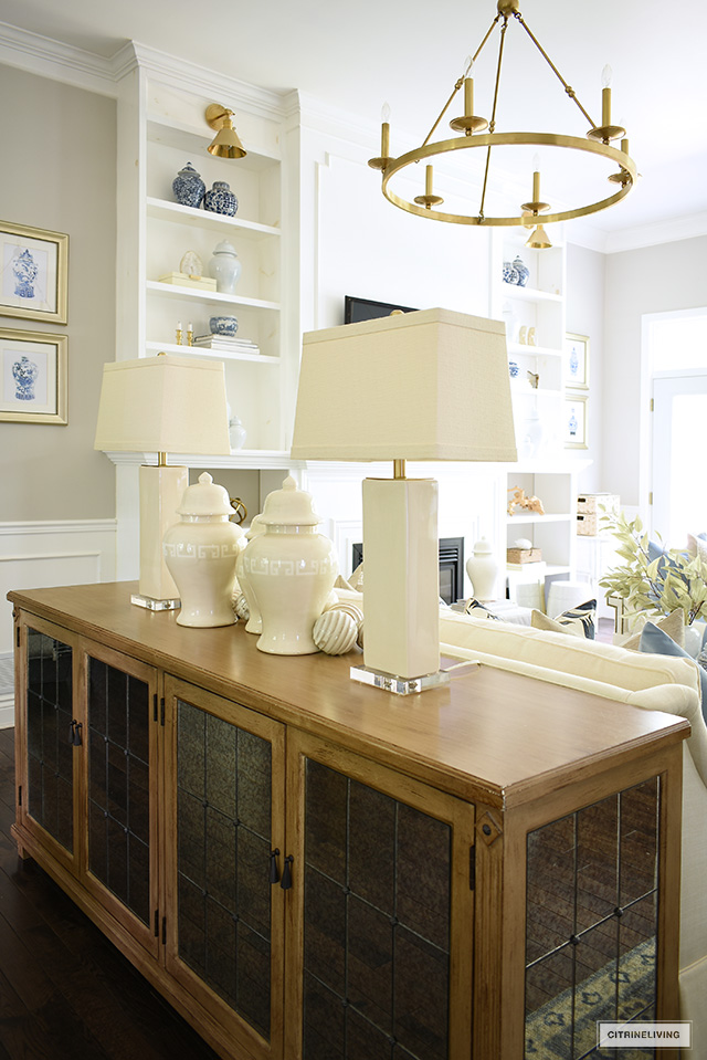 Living room decorated for fall, console table styled with ginger jars, decorative balls and flanked by a pair of lamps.