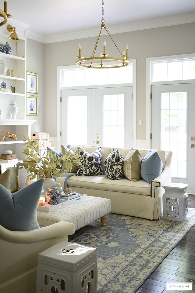 Fall living room styled with white sofas, blue and beige designer pillows and simple fall touches.