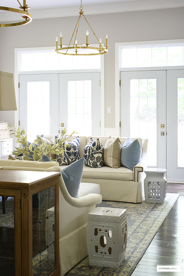 Living room decorated for fall with designer pillows, faux fall foliage and simple accessories.