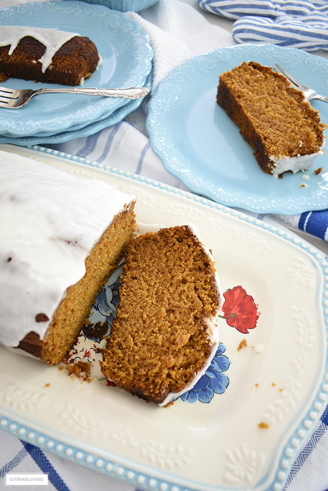 Pumpkin loaf recipe with glaze, styled on beautiful blue dishes.