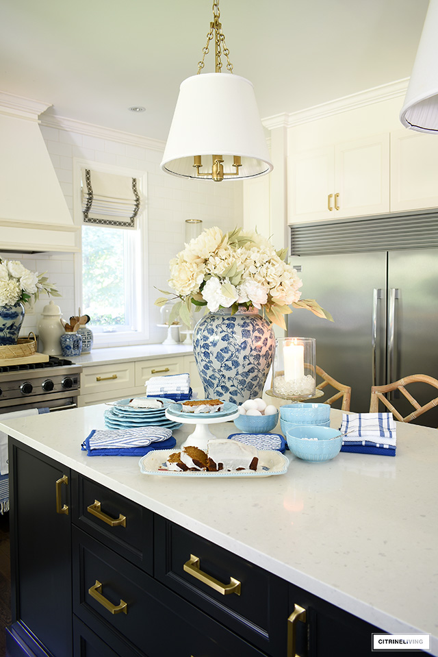 Kitchen island styled for fall with light blue dishes and kitchen towel set.
