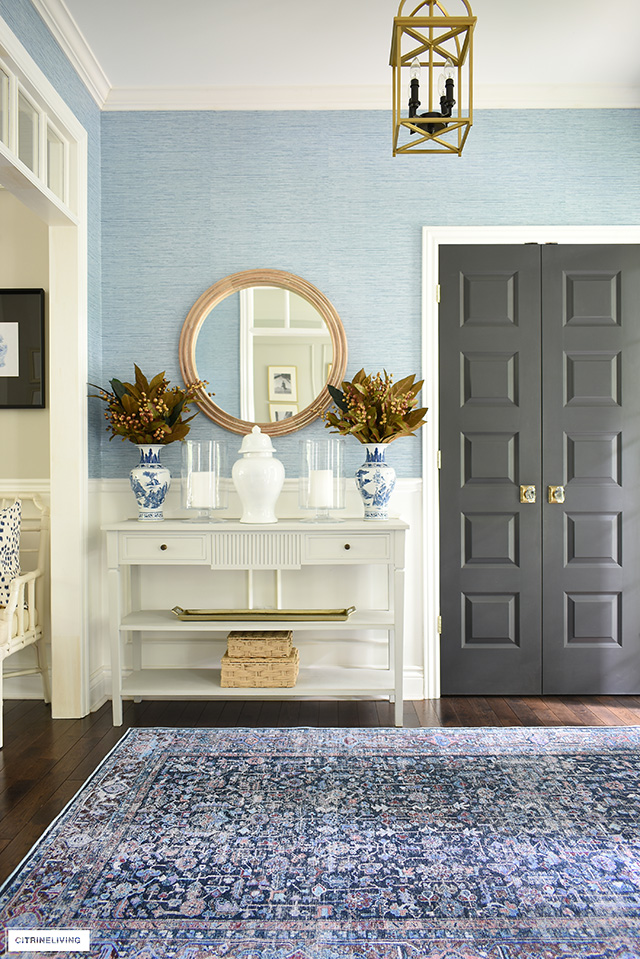 Fall entryway decor with a beautiful navy blue pattern rug, woven textures and warm gold tones.