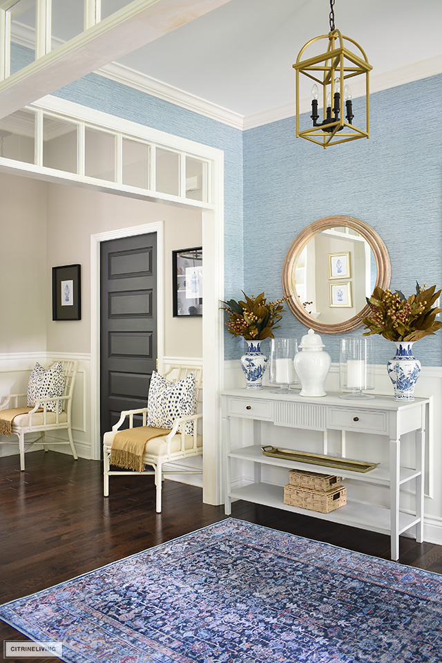 Entryway decorated for fall with simple seasonal touches in blue, white and gold.