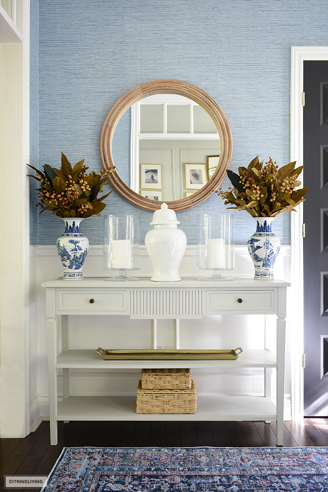 Fall console table styling with faux fall foliage, blue and whit chinoiserie, woven and wood textures and gold accents.