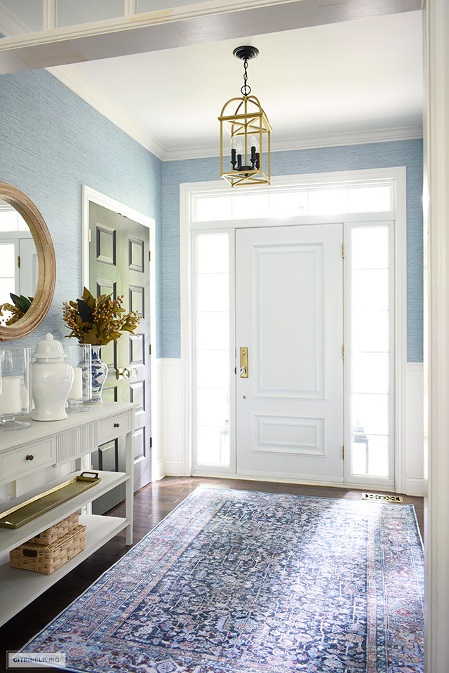 A beautiful navy blue boho-inspired rug styled in a fall entryway.