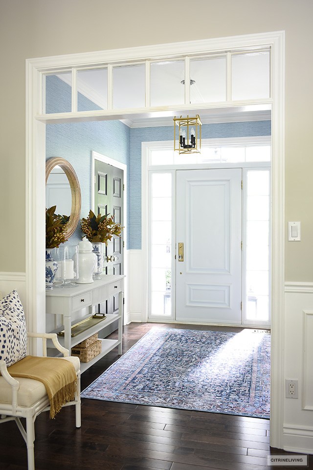 Fall entryway decorated with a beautiful navy blue washable rug and console table styled with simple seasonal touches.