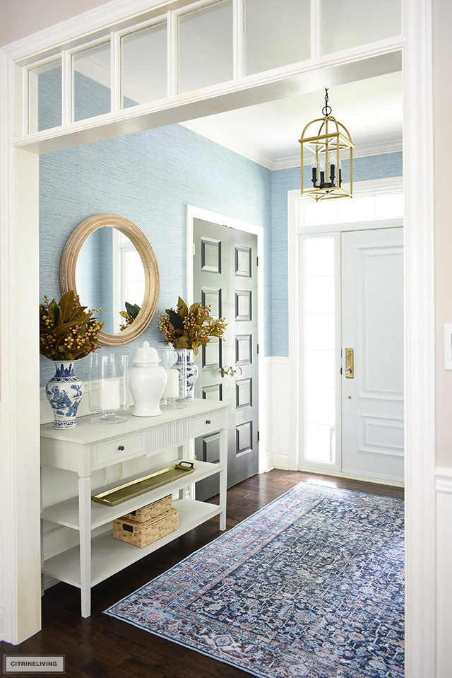 Foyer decorated for fall with a beautiful navy blue bohemian inspired rug, gold-toned accessories, faux foliage and blue and white chinoiserie.
